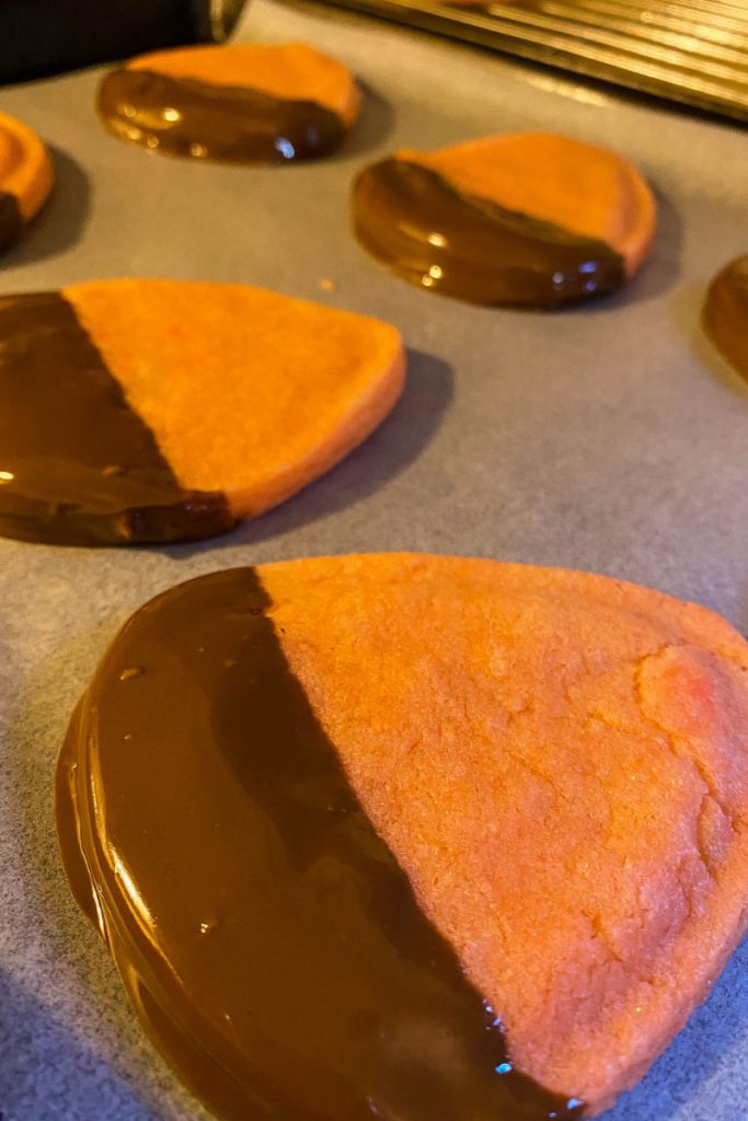 Candy corn decorated sugar cookies dipped in chocolate for Halloween.